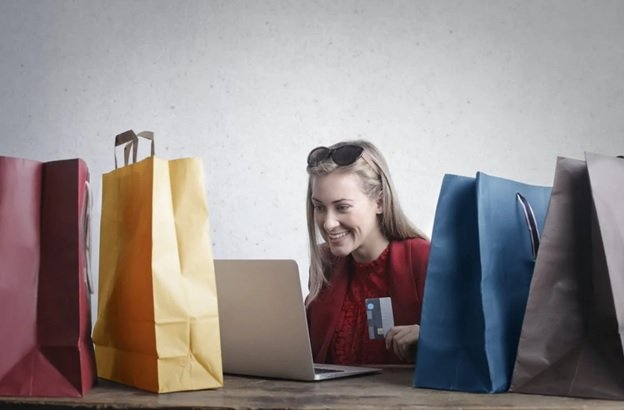 A Blonde Woman In A Red Shirt With Black And Brown Sunglasses On Her Head Is Smiling At Her Laptop Screen With Her Credit Card In Her Hand, Presumably Ordering Items Online As She Is Surrounded By Red, Yellow, Blue, And Grey Gift Bags From Her Previous Online Purchases