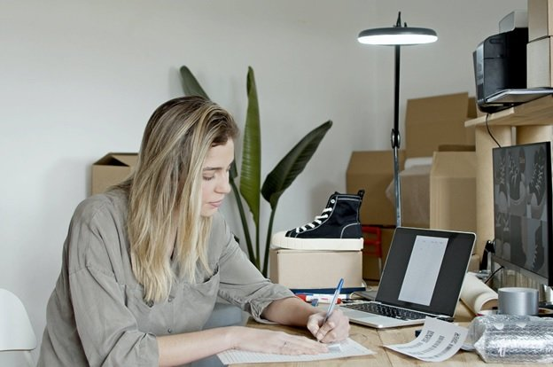 A Woman Is Writing Down Minimum And Maximum Prices For Her Amazon Repricer Tool