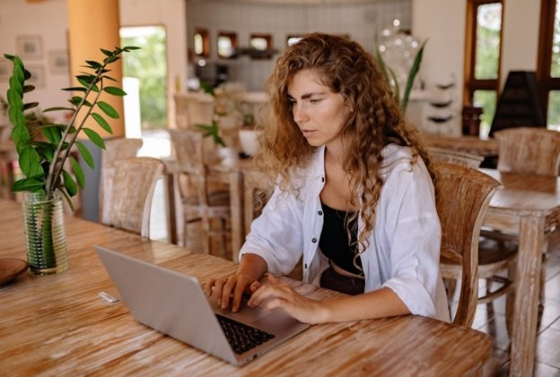 A Young Brown-Haired Woman Wearing A White Shirt Is Using An Amazon Repricer Tool On Her Grey Laptop While She Sits In A Cozy Vintage Cafe With Plants, Bowls, And Vintage Furniture Around Her