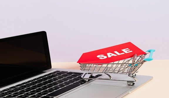 Miniature Cart On A Laptop Displaying Online Sales